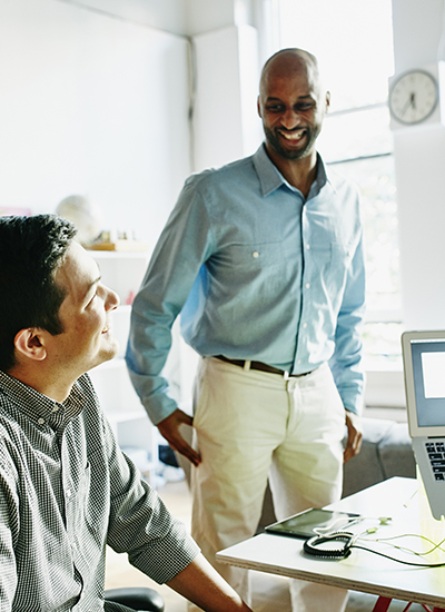 Two smiling coworkers discussing project at desk in startup office